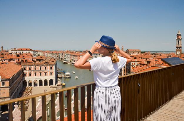Chica parada en la orilla de un puente mirando el mar de Italia