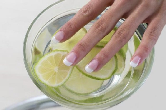 Girl dipping her fingers into a bowl of water and lemon juice