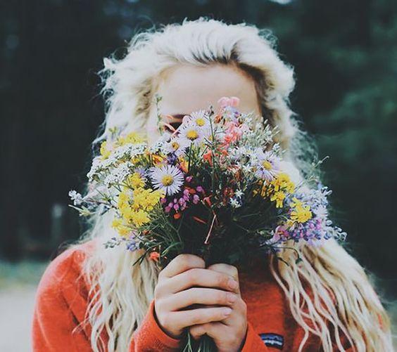 Chica rubia sosteniendo ramo de flores