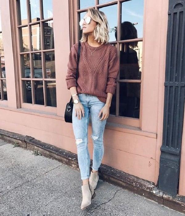 Chica usando jeans y suéter color rosa palo