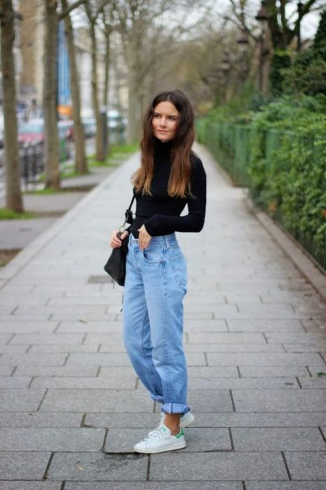 Chica usando mom jeans y blusa negra de manga larga