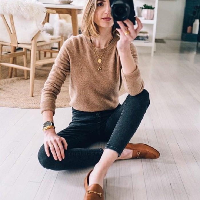 Chica usando jeans negros, mocasiones y suéter cafés