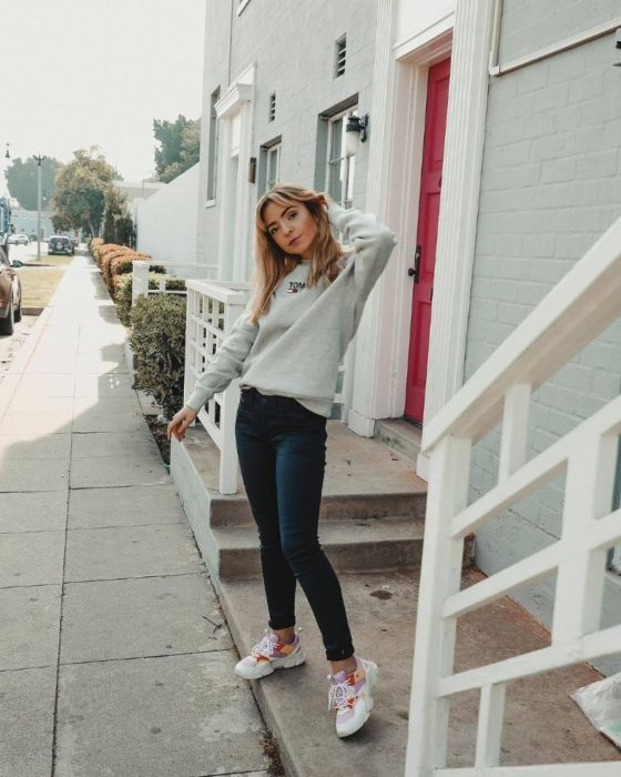 Girl wearing skinny jeans with white sweater and tennis shoes