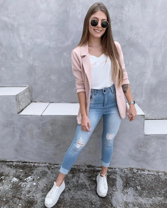 Girl wearing skinny jeans, white low top sneakers, pink blazer and white shirt