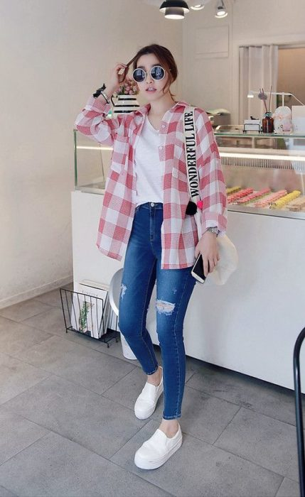 Girl wearing skinny jeans with a white shirt and plaid shirt