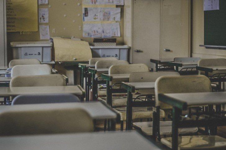Aula de alumnos vacia con butacas acomodadas a los costados
