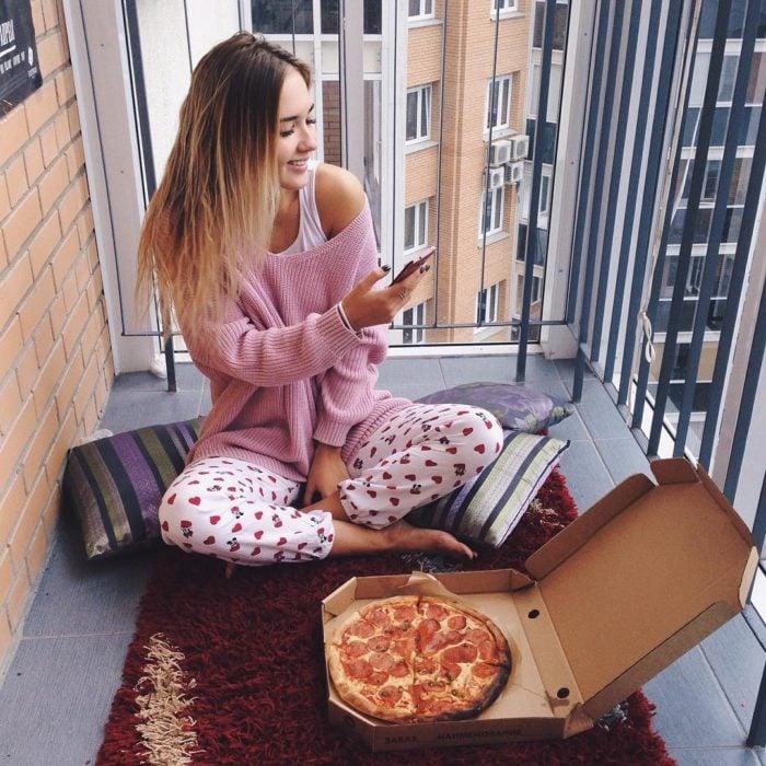 Chica en el balcón comiendo pizza