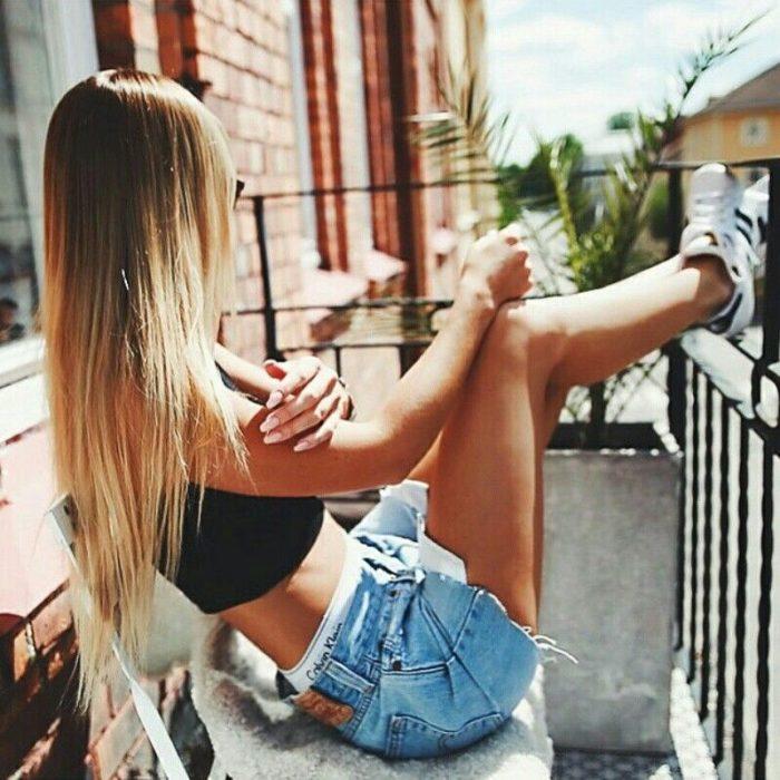 Chica tomando el sol desde un balcón
