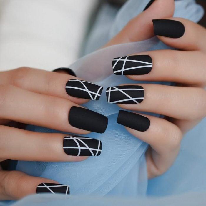 Manicura en color negro con lineas blancas