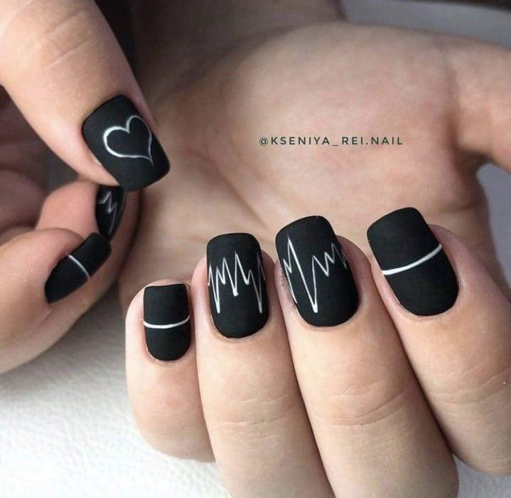 Manicura en color negro con diseño de lineas en blanco y efecto mate