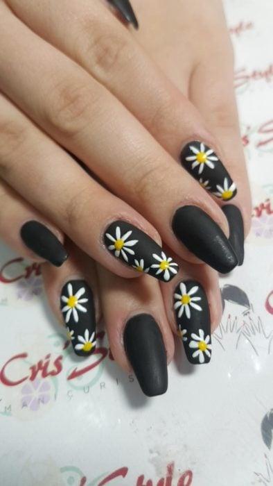 Manicura en color negro y diseño de margaritas con efecto mate