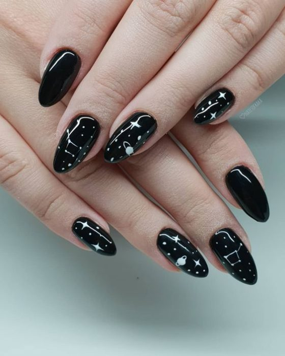 Manicura en color negro con diseño de estrellas en color blanco