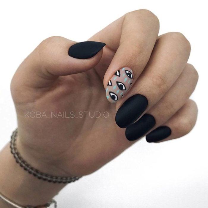 Manicura en color negro en efecto mate y diseño de ojos en el dedo indice