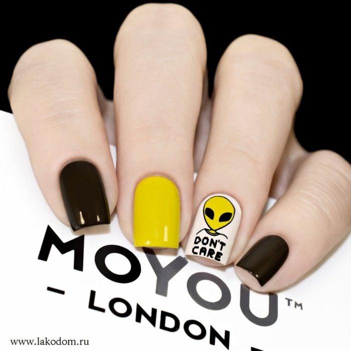 Manicura en color negro un dedo en color amarillo y un ovni