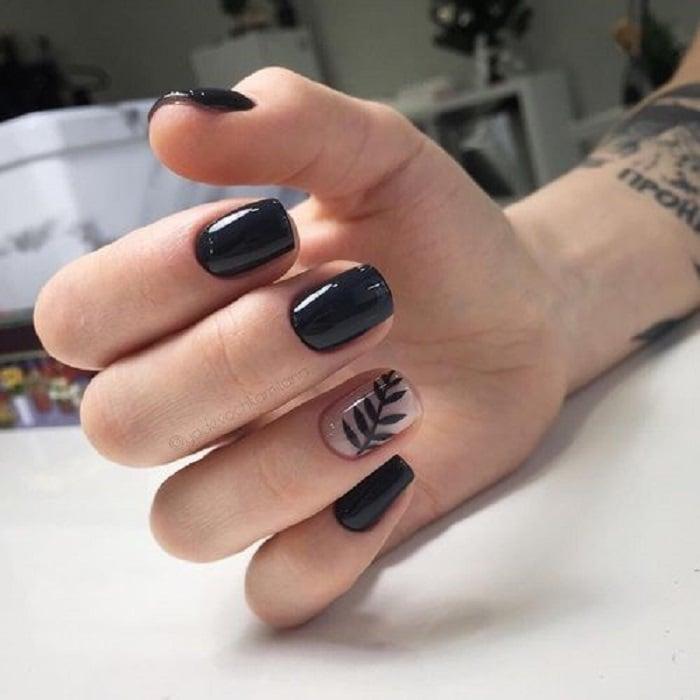 Manicura en color negro con diseño en dedo anular de una hoja