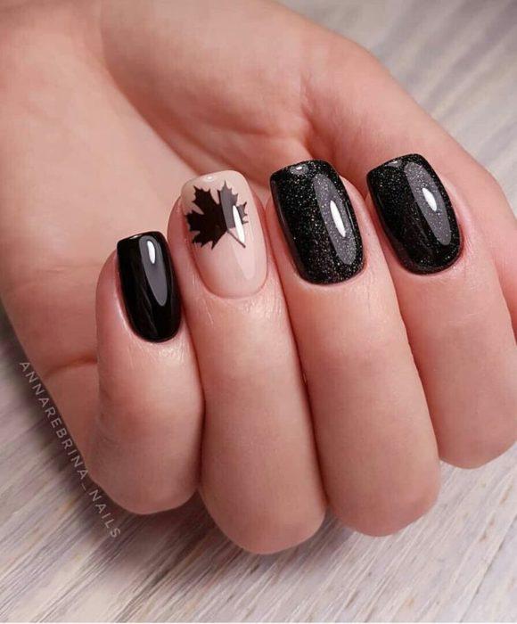 Manicura en color negro con diseño en dedo anular de una hoja de maple