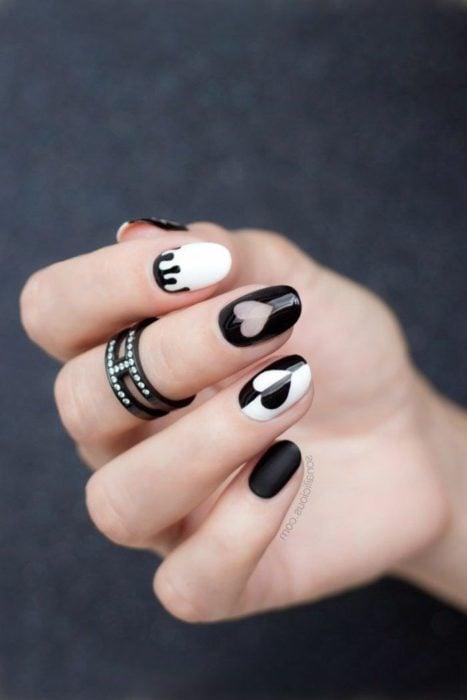 Manicura en color negro y blanco con diseño de corazones
