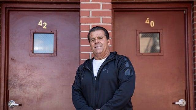 Mario Salerno posando para una foto frente a las puertas de su edificio