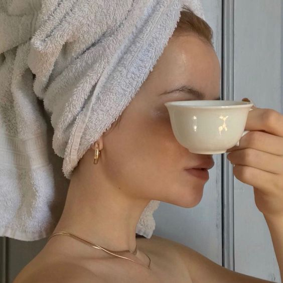 Girl with a towel on her head covers her face with a cup