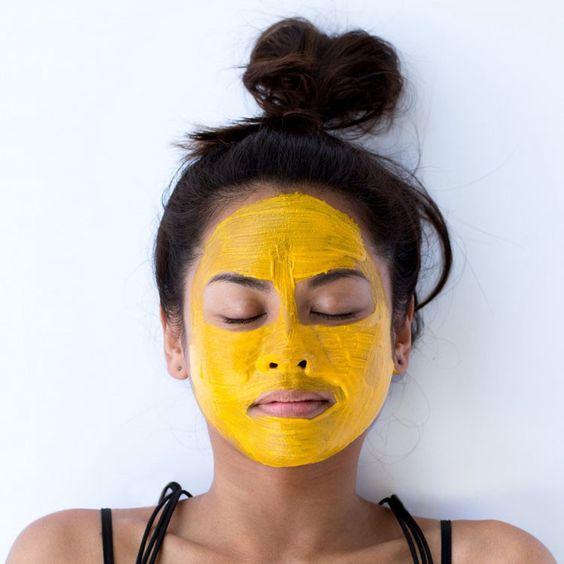 Chica con mascarilla de cúrcuma en el rostro