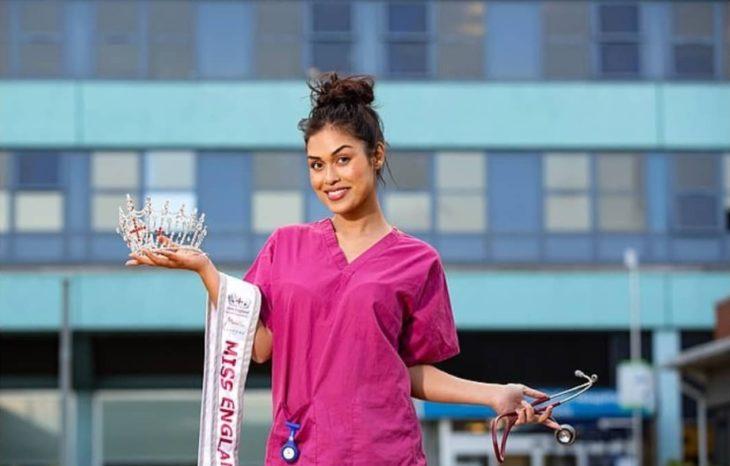 Bhasha Mukherjee vistiendo su uniforme de médico y con su corona y banda de Miss Inglaterra