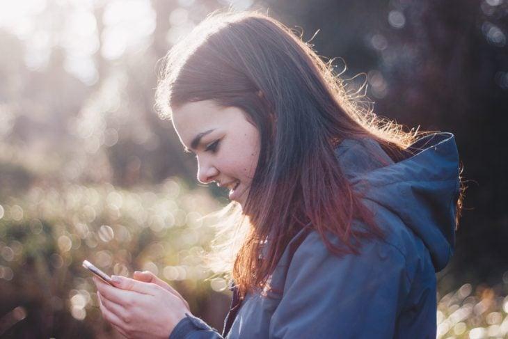 Chica de cabello castaño mirando su celular