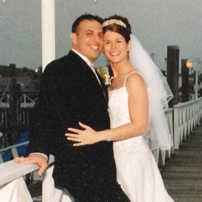Mujer abrazando a su esposo el día de su boda durante una sesión de fotos en un puente
