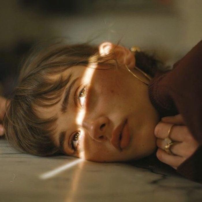 Chica triste acostada en el piso