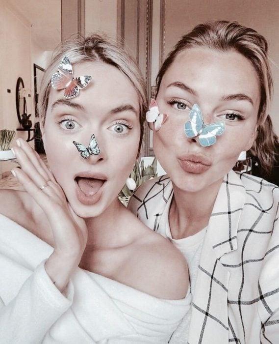 Chicas hacen caras graciosas con mariposas en la cara