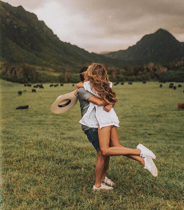 Hombre carga a su novia en brazos mientras dan vueltas en un campo verde y hermoso