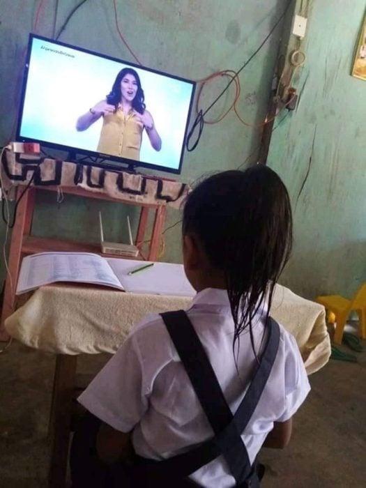 Niña se pone su uniforme y se peina para sus clases online
