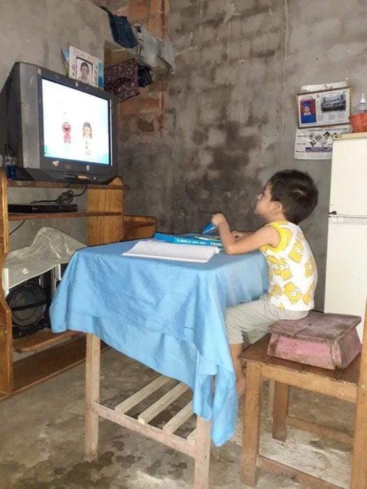 Niño pequeño sentado en una silla haciendo tarea