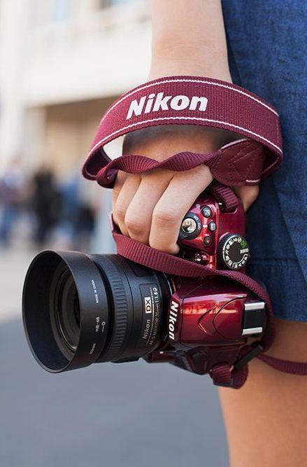 Chica cargando una cámara Nikon con listón en color vino
