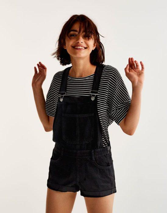 Chica usando un overol negro