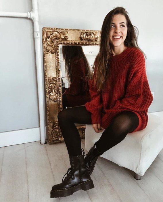 Chica usando un vestido/suéter guinda con medias