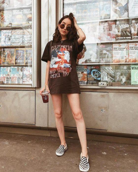 Chica con look grunge con blusa negra y vans blancos con negro de cuadros