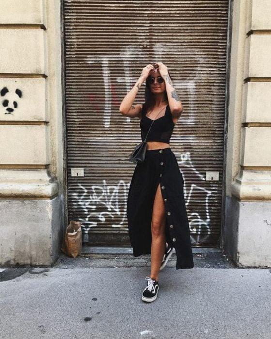 Chica delgada con gafas oscuras viste falda larga y blusa de tirantes negra