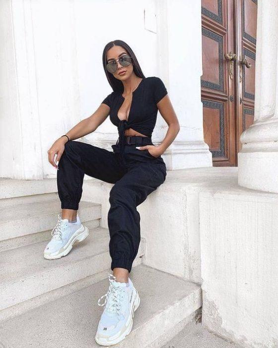 Chica con gafas de sol sentada en escalón viste blusa negra y pantalón negro con tenis blancos