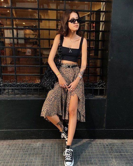 Chica posando con falda larga de animal print, crop top negra y tenis converse