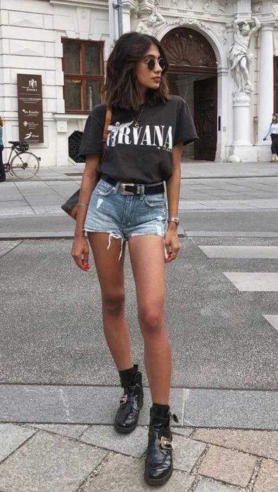 Chica con blusa de nirvana color negra y short de mezclilla con cinto y botas engras