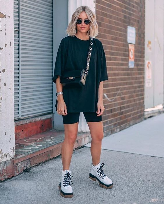 Chica rubia con melena usa blusa holgada negra con short negro y botas blancas