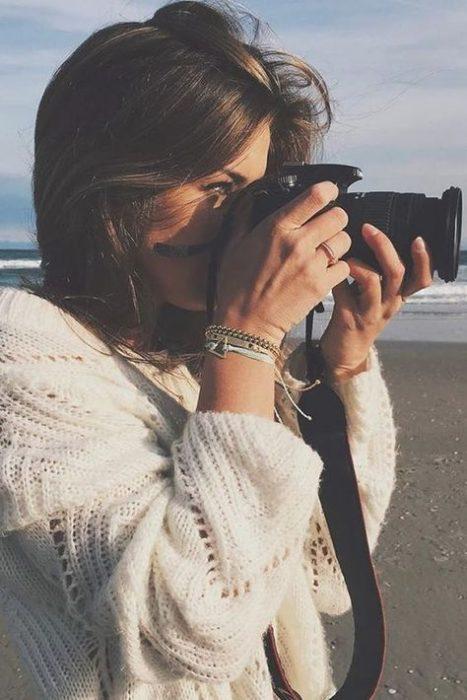Chica tomando fotografías con su cámara profesional