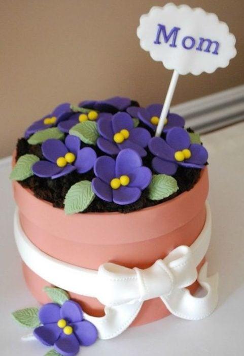 Pastel en forma de macetita con flores moradas para mamá