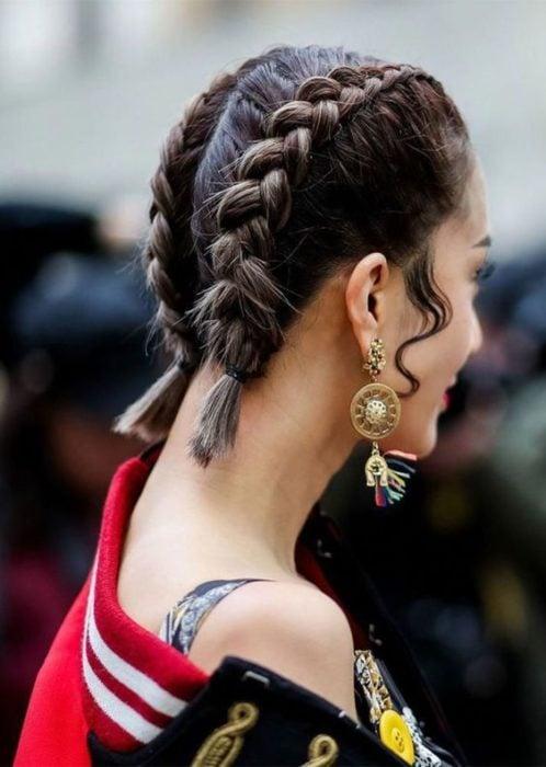 Chica con el cabello corto sujetado en dos trenzas