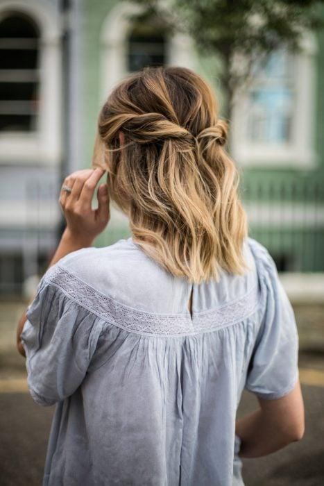 Chica de cabello corto sujetado en una media coleta con torciditos a los lados