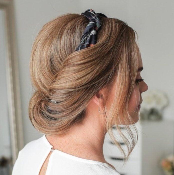 Chica con el cabello corto sujetado con una diadema en un chongo bajo