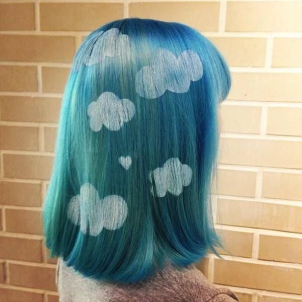 Chica con el cabello teñido de color azul con nubes