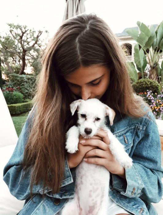 Mujer cargando a perrito blanco y dándole un beso