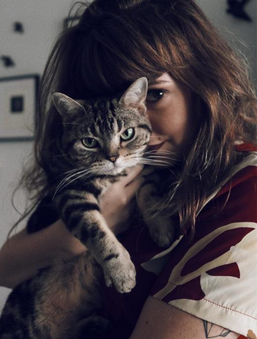 Mujer cargando a gato rayado de ojos verdes
