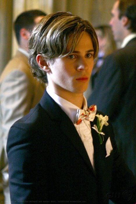 Eric Van Der Woodsen personaje de la serie Gossip Girl usando un traje durante una fiesta